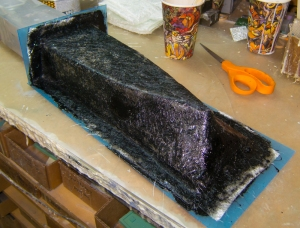 Fiberglass mat applied over gel coat